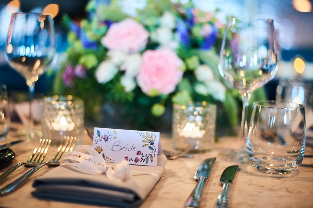 Table set for wedding with flowers and bride place holder