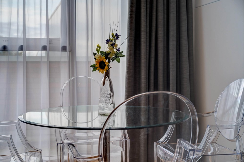 Glass table with flowers in Clarity room at Apex City Quay Hotel