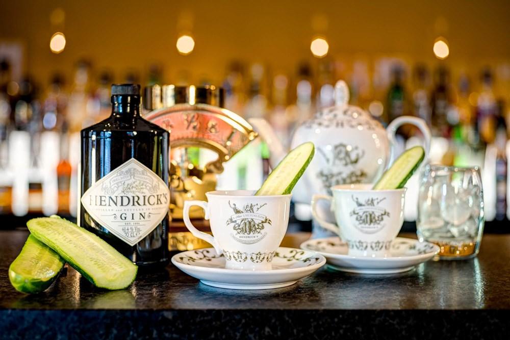 Teacups with Hendricks gin and cucumber on bar