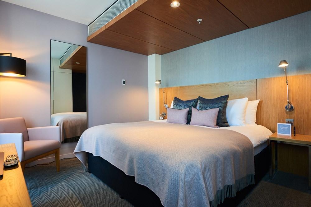Junior Suite bedroom with king-size bed at Apex City of London Hotel