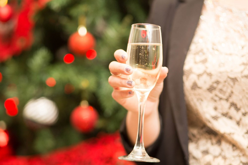 Female guest holding glass of fizz with Christmas tree in background