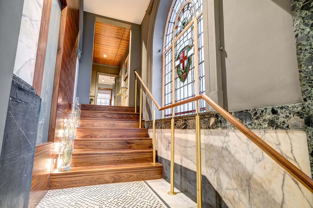 Grand Suite hallway with stairs and stained glass window at Apex Temple Court Hotel