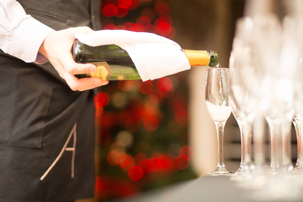 Waiter pouring bottle of fizz into flute glasses with Christmas tree in background