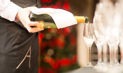 apex staff member pouring bottle of fizz