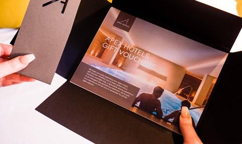 Hands holding an Apex Hotels gift voucher