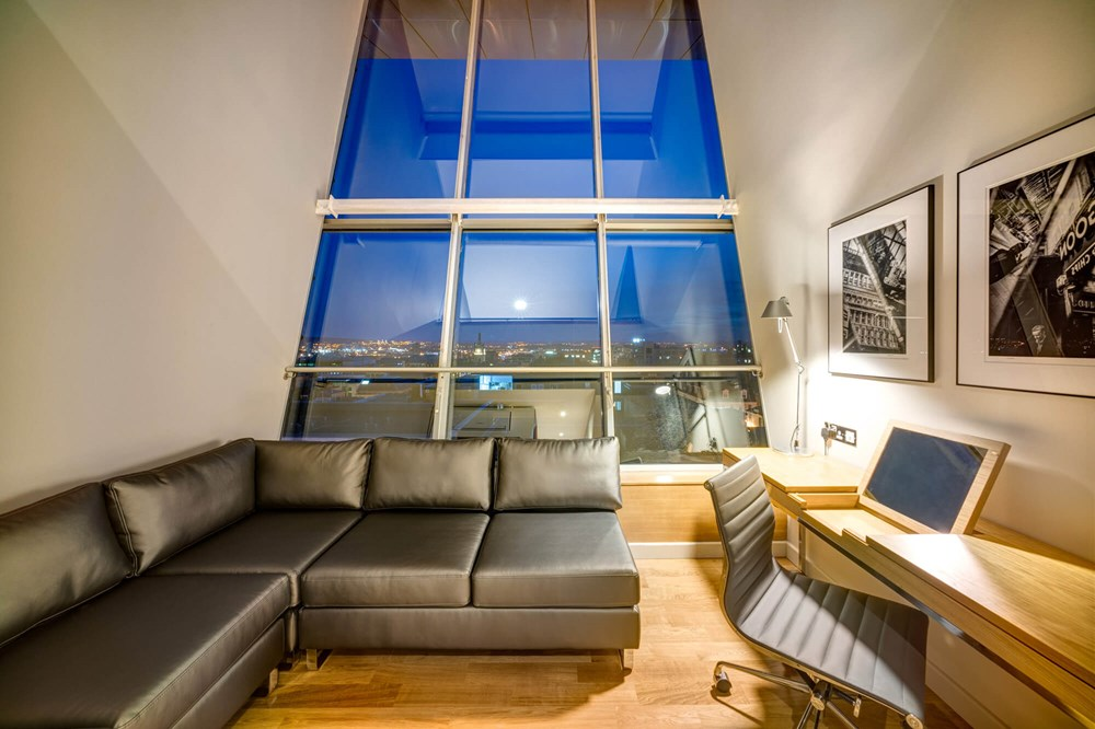 Duplex Suite lounge area with sofa and TV and city view