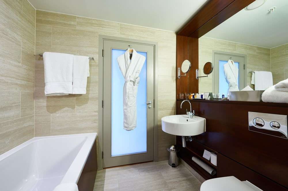 Junior Suite bathroom with bath and robes hanging on door at Apex City of London Hotel
