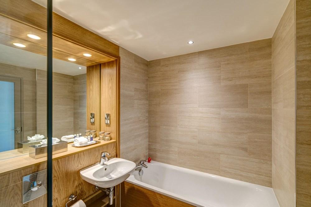 Bath tub next to sink in bathroom