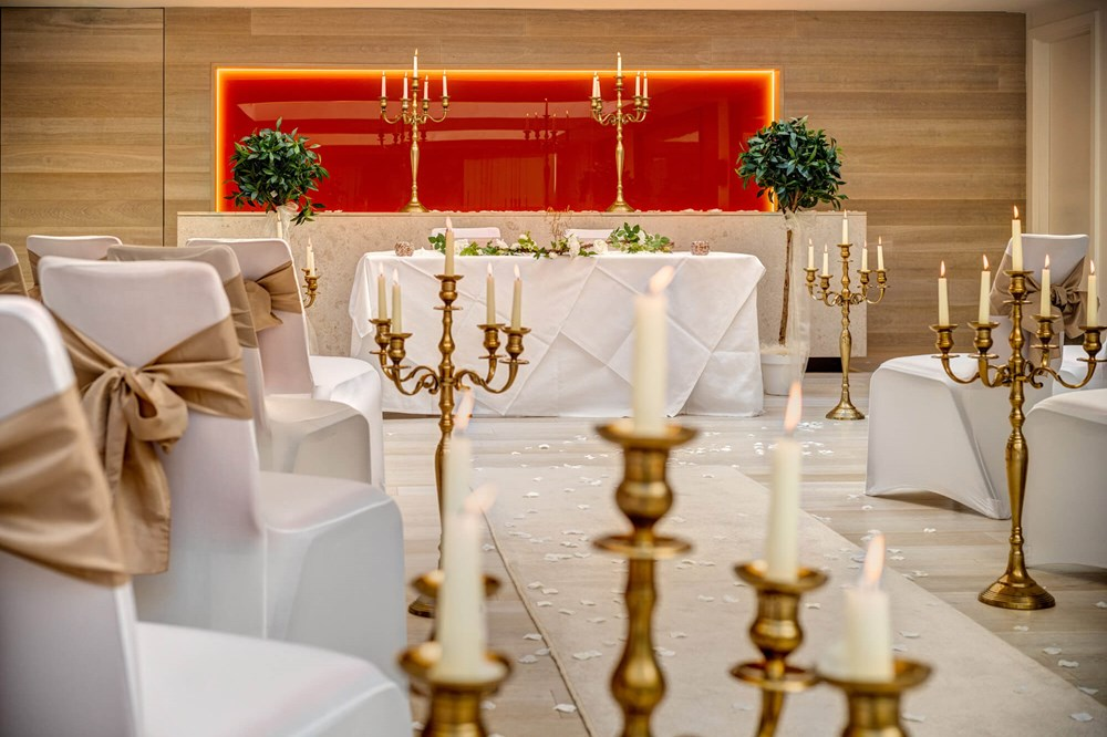 The Atrium at Apex City of Bath Hotel set for wedding with aisle, white seats and gold candles