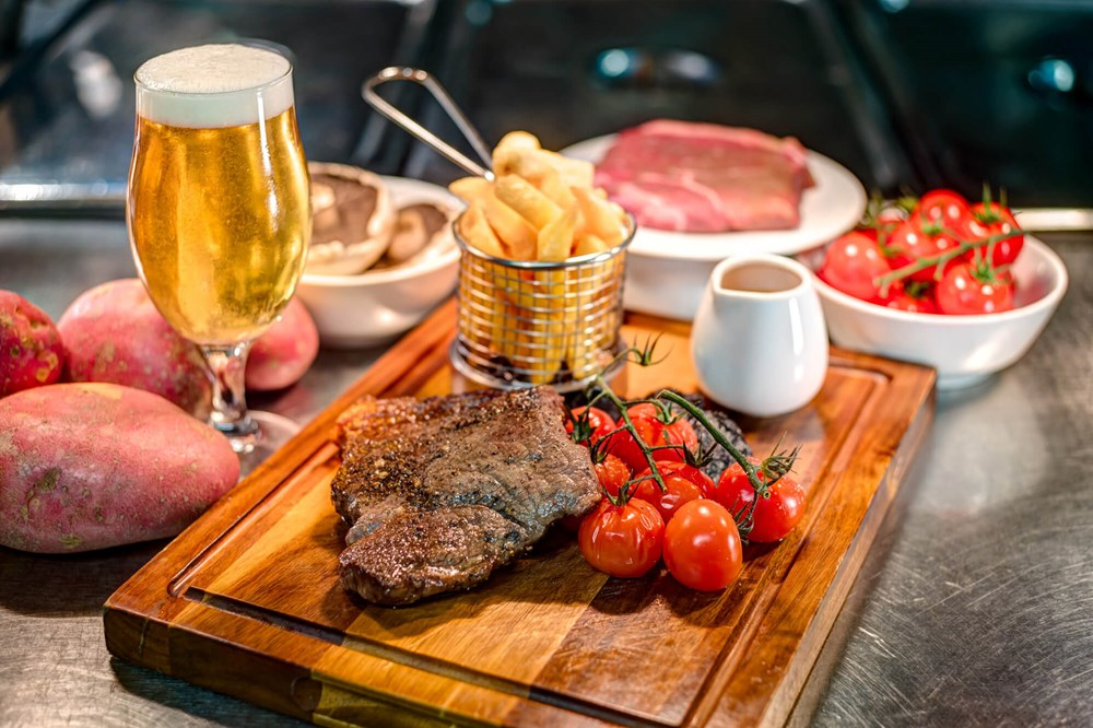 Steak with chips, tomatoes and beer