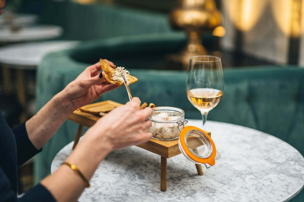 Person using knife to put spread on bread and glass of white wine