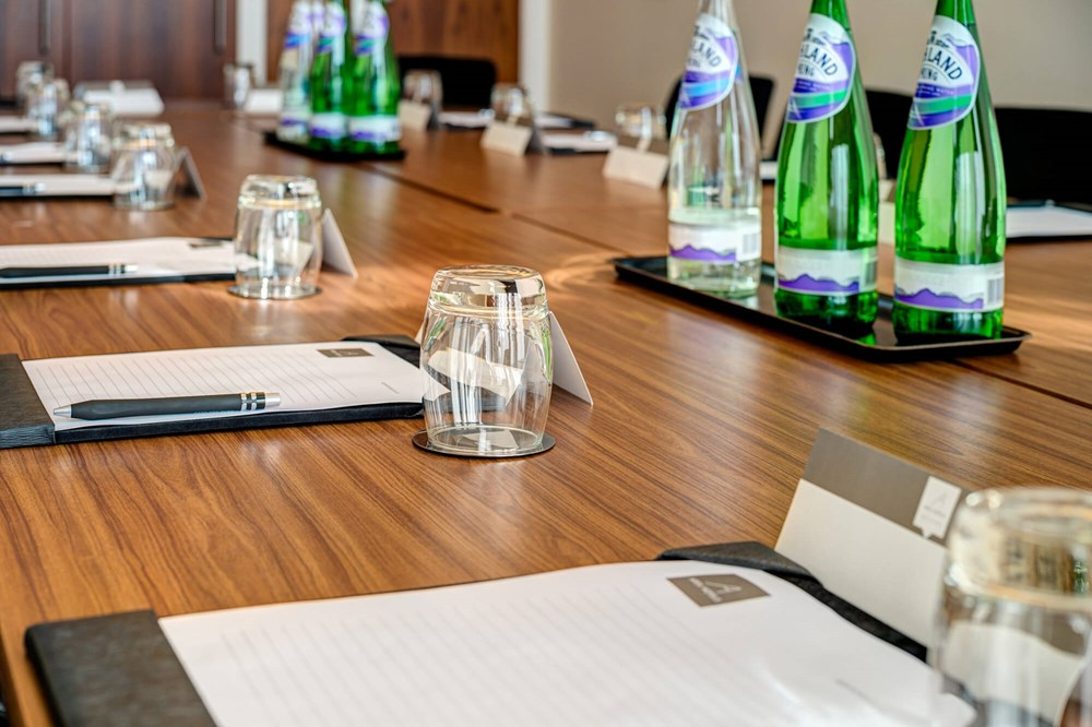 Close up of table set for meeting with notepads and water