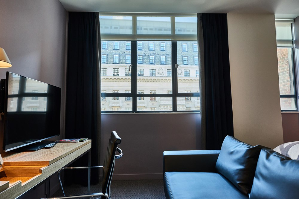 Superior Room seating area with sofa, desk, chair and TV at Apex City of London Hotel