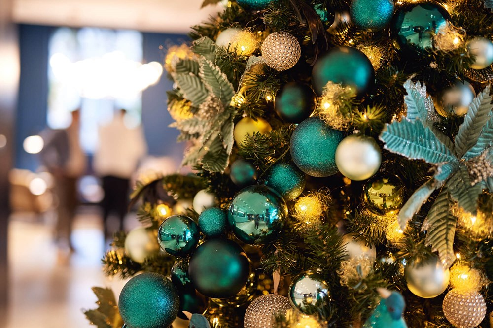 Close up of Christmas tree with green, gold and blue baubles