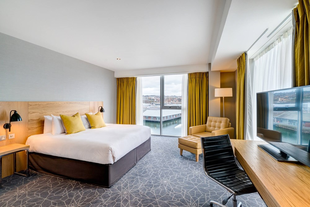 Quay View Superior Room with double bed and floor-to-ceiling windows at Apex City Quay Hotel & Spa