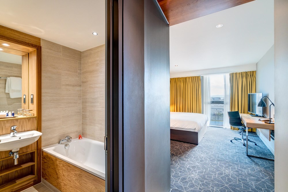 Bathroom with tub and bedroom with king-size bed