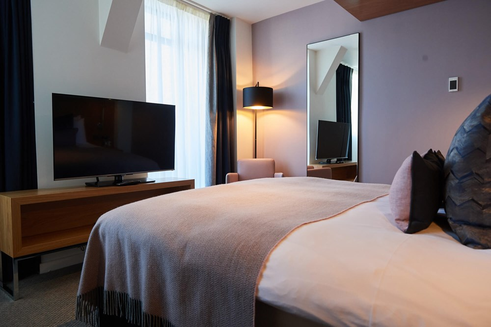 Junior Suite bedroom with king-size bed and TV at Apex City of London Hotel