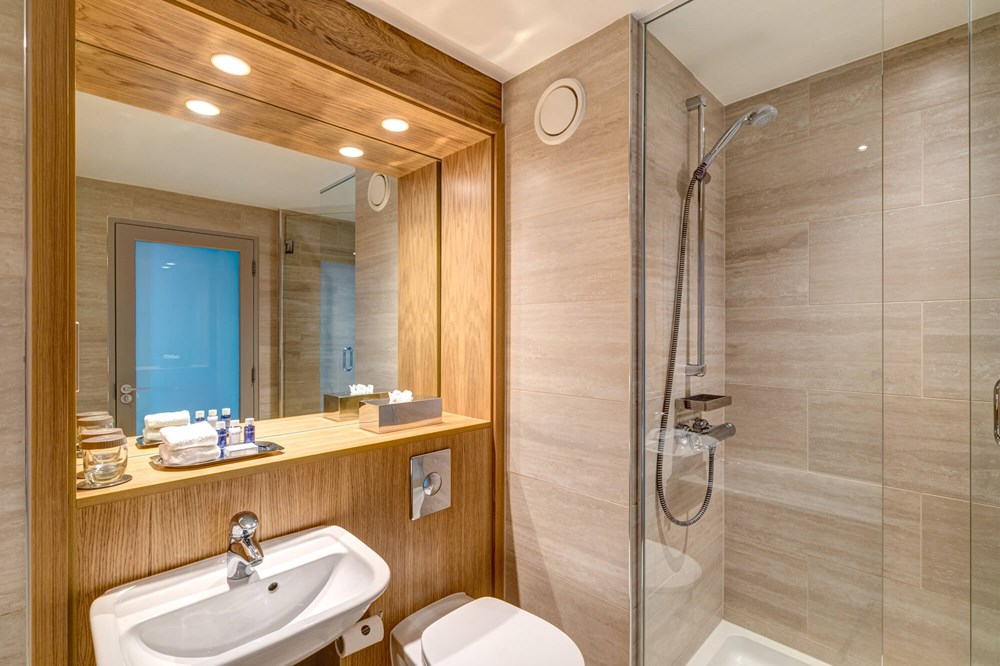 Family Room bathroom with walk-in shower at Apex City Quay Hotel & Spa