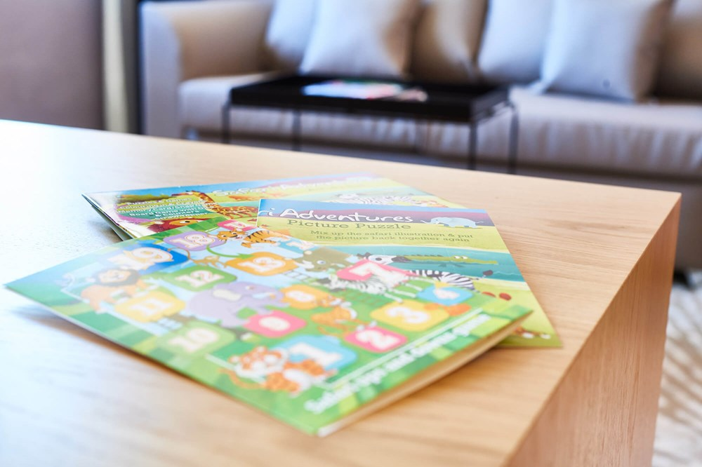 Kids' colouring books on table in Family Room at Apex City of London Hotel