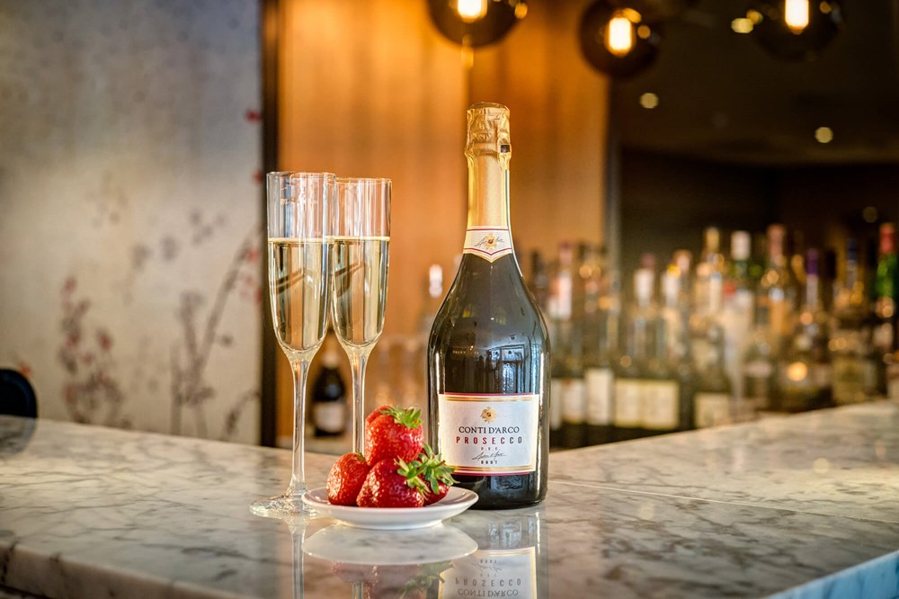 Two flutes of fizz with bottle and strawberries on the bar