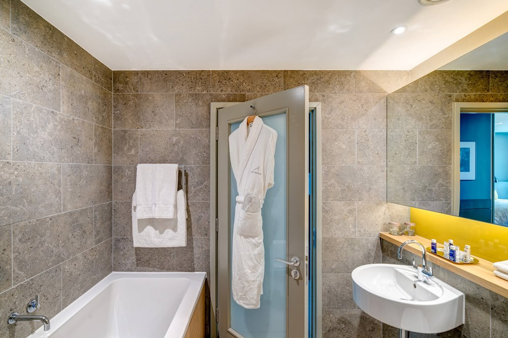 Deluxe Room bathroom with bath and robe hanging on back of door