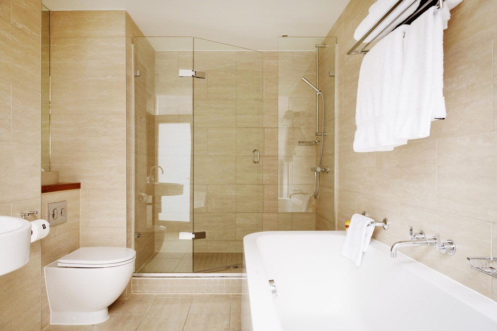 Family Room bathroom with walk-in shower and bath at Apex City of London Hotel