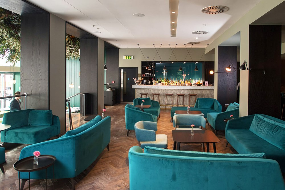 The Lampery bar with plush velvet sofas and parquet flooring