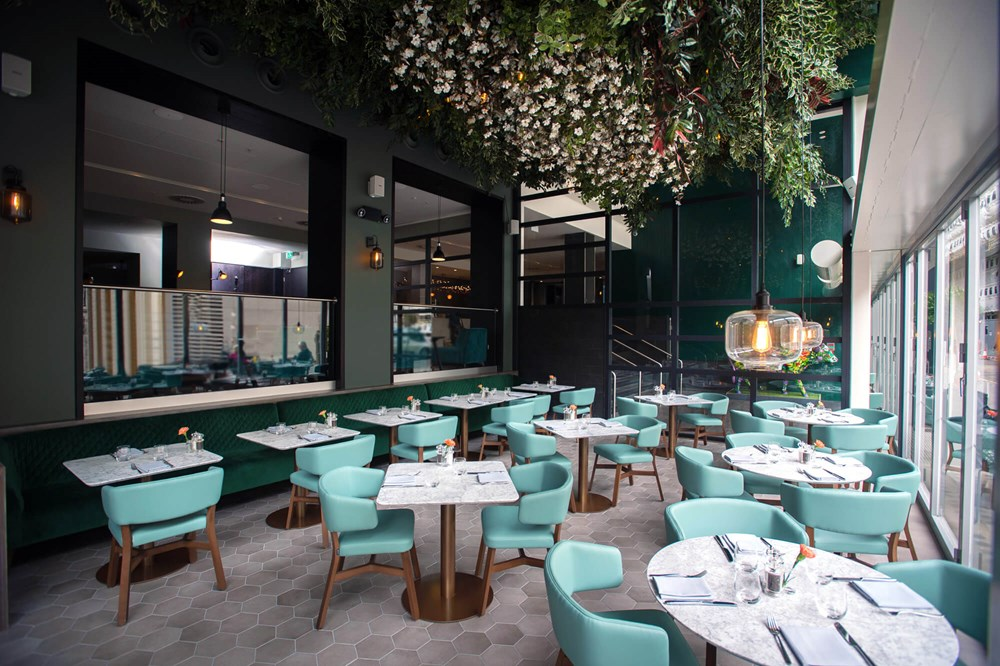 The Terrace at The Lampery restaurant with tables, chairs and floral canopy above