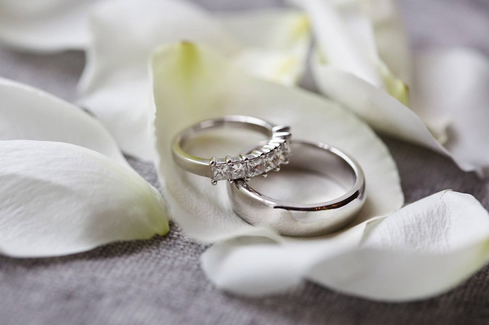 Two silver wedding rings on white rose petals