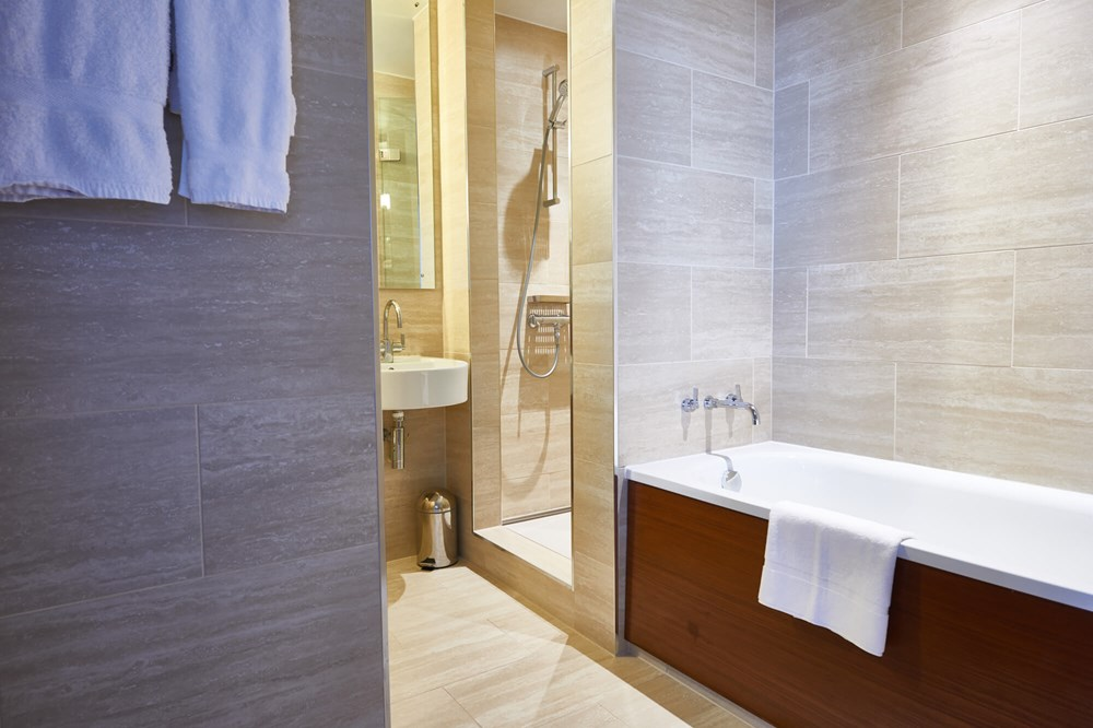 Deluxe Room bathroom with bath and walk-in shower at Apex City of London Hotel